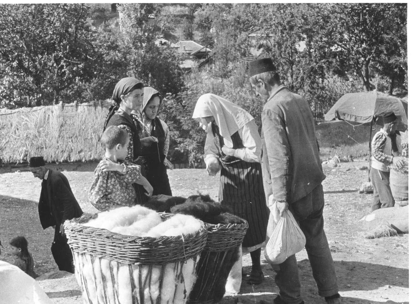 Orthodox woman at the Labuniste market looking at wool for sale next to Muslim man on her left, he is a farmer who used to have a kafana for twenty years in the village, now he carts wool on his horse. ( Vlach woman from Labuniste selling her wool). Village: Labuniste Date: 1962