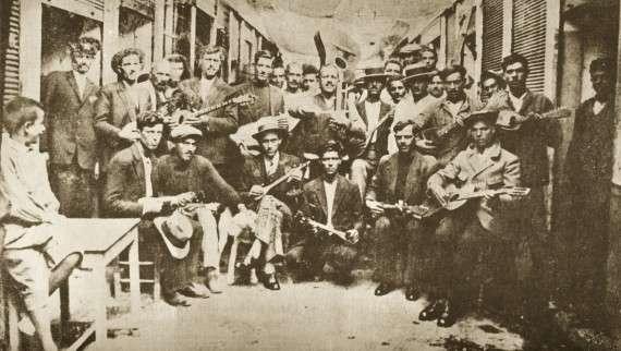 Ρεμπέτες στο Καραϊσκάκη, Πειραιάς (1933). Αριστερά ο Μάρκος Βαμβακάρης με μπουζούκι, στο κέντρο ο Μπάτης με την κιθάρα..