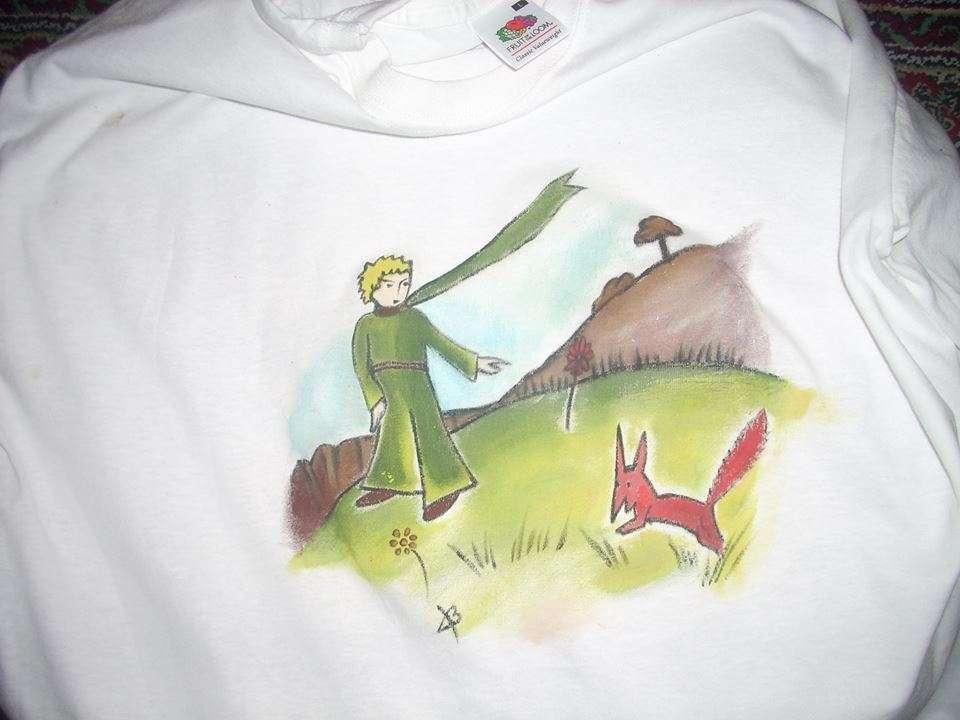 """-Τι σημαίνει """"εξημερώνω'? ρώτησε ο μικρός πρίγκηπας. -Αυτό σημαίνει ''δημιουργώ δεσμούς''. απάντησε η αλεπού. (ζωγραφιά σε ανδρικό t-shirt) ...για την Χριστίνα."""