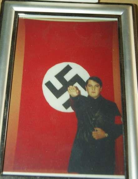 Ο Χρήστος Παππάς, νεαρός, να χαιρετίζει ναζιστικά, μπροστά σε μια τεράστια σημαία με τον αγκυλωτό σταυρό, φορώντας κάτι σαν στολή και χτενισμένος ανάλογα για να μοιάζει με τα πρότυπά του, τους αξιωματικούς των SS...