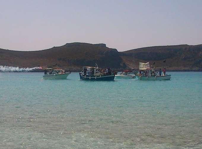 Στιγμιότυπο της Διαμαρτυρίας: Κάποια καΐκια του  ΑΛΙΕΥΤΙΚΟΥ ΣΥΛΛΟΓΟΥ ΕΛΑΦΟΝΗΣΟΥ -   από τους μεγαλύτερους αλιευτικούς στόλους στην Ελλάδα – έχουν προσορμίσει στο Σίμο και προσεγγίζουν στο Δύορμο αμμογυάλι  της Διαμαρτυρίας  (φωτ. Χρ. Κοντραφούρη)