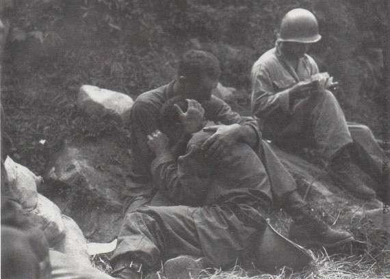 Αυτή η φωτογραφία δημοσιεύτηκε κατά τους πρώτους μήνες του πολέμου της Κορέας. Ο στρατιώτης κλαίει επειδή έχασε έναν σύντροφο. Ένας άλλος, πίσω, καταγράφει τις απώλειες.