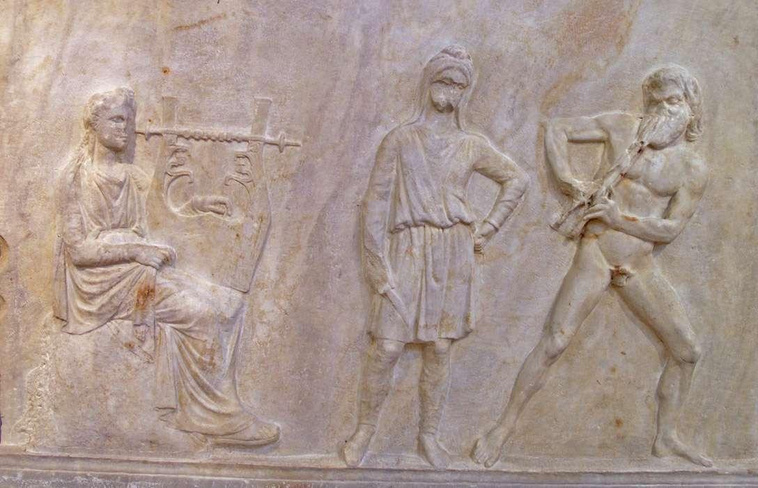 Ο Απόλλωνας (αριστερά) συναγωνίζεται με το Μαρσύα (δεξιά) που σε λίγο θα ηττηθεί και θα τιμωρηθεί από τον Σκύθη με το μαχαίρι. Ανάγλυφο, από την βάση της Μαντινείας μέσα 4ου αι. π.Χ.