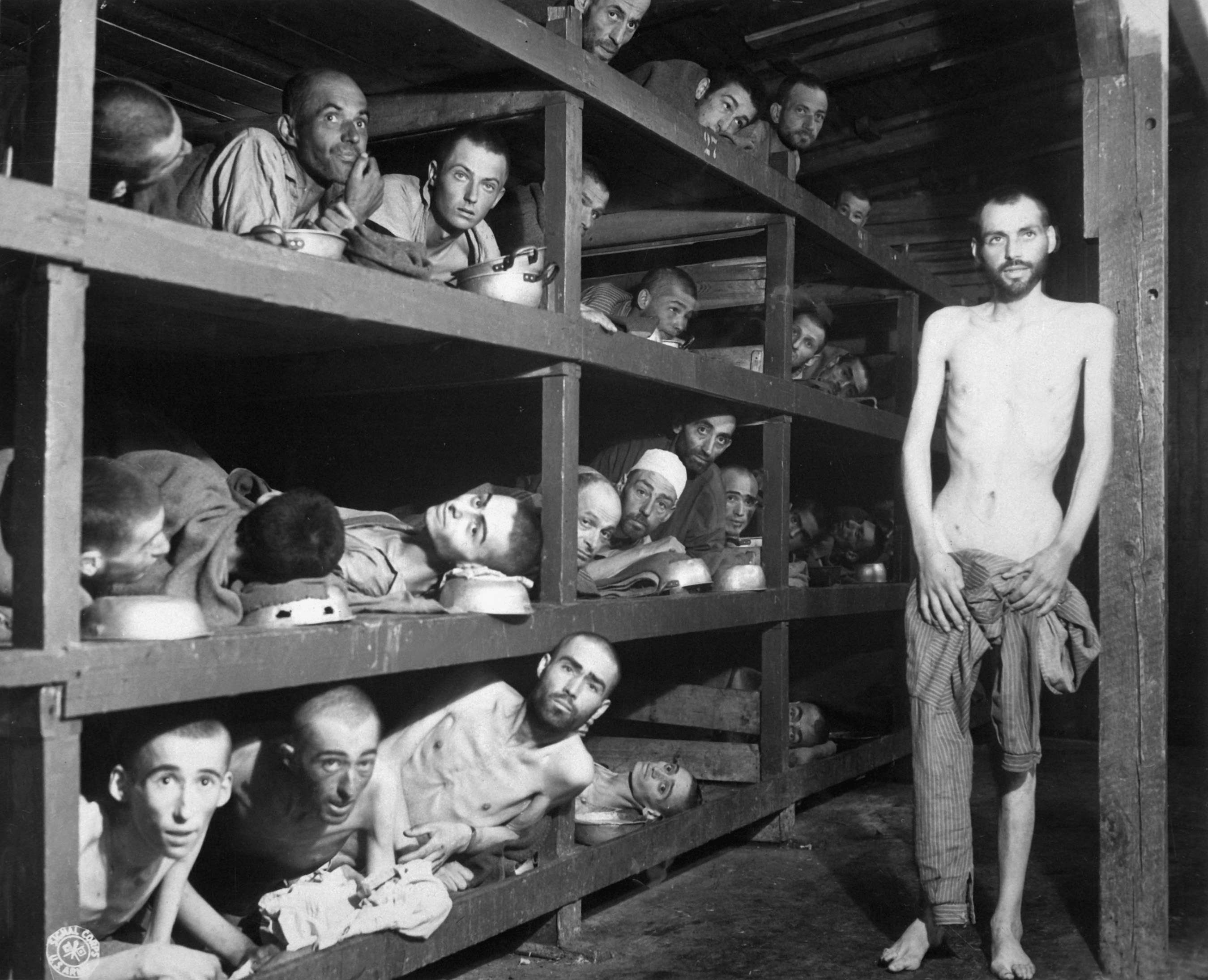 These are slave laborers in the Buchenwald concentration camp near Weimar; many had died from malnutrition when U.S. troops of the 80th Division entered the camp. The very ill man lying at the back on the lower bunk is Max Hamburger, who had TBC and severe malnutrition. He recovered and became a psychiatrist in the Netherlands. Second row, seventh from left is Elie Wiesel. Photograph taken 5 days after rescue.