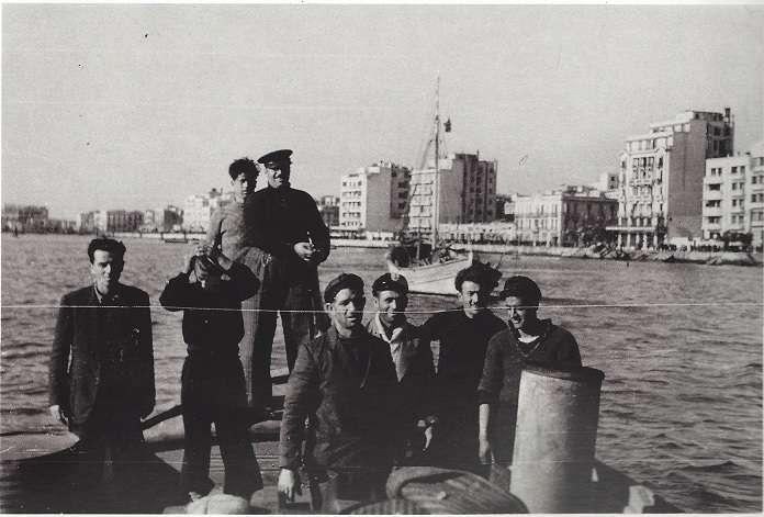 """1944, απελευθέρωση. Ατμάκατος με άνδρες του ΕΛΑΝ Χαλκιδικής μπροστά από το λιμάνι της Θεσσαλονίκης. Στα δεξιά το ξενοδοχείο """"Ματζέστικ"""" που επιτάχθηκε από το ΕΛΑΝ. Αριστερά φαίνεται ο Ιερισσιώτης Δημήτριος Α. Λαγόντζος, μπροστά στο κέντρο ο Γεώργιος Α. Λαγόντζος, και δίπλα του πίσω, πιθανόν, ο Δημήτριος Λαζαρίνης. Φωτογραφία από το λεύκωμα """"Θεσ/κη 1944, Τα φωτογραφικά ντοκουμέντα του J. Lieberg""""."""