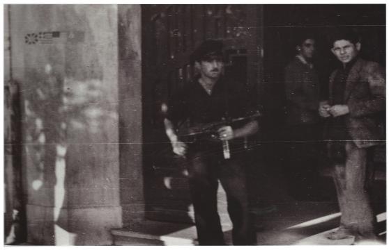 """Ναύτης της VI Μοίρας του ΕΛΑΝ φρουρεί τα γραφεία του Διεθνούς Ερυθρού Σταυρού στην οδό Λεωφόρος Νίκης 41 στη Θεσσαλονίκη. Στον τοίχο οι 3 συμμαχικές σημαίες, 02 Νοεμβρίου 1944. Φωτογραφία από το λεύκωμα """"Θεσ/κη 1944, Τα φωτογραφικά ντοκουμέντα του J. Lieberg""""."""