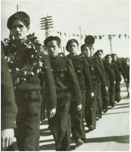 Παρέλαση του ΕΛΑΝ στη Θεσσαλονίκη. Διακρίνονται οι Ιερισσιώτες: Αριστείδης Γιώργου στεφανωμένος από τον κόσμο & πίσω του ο Κων/νος Σουλτάνης. Φωτογραφία από το αρχείο του Λάζαρου Ακκερμανίδη.
