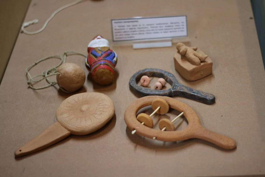 Σείστρο (Κουδουνίστρα) πλαταγή. Διασκέδαζε και ηρεμούσε τα μωρά, έδιωχνε τα κακά πνεύματα. Σείστρο από πηλό. Πήλινοι δίσκοι. Ανθρωπάκι 3ου αιώνα. Πήλινη κουδουνίστρα με χερούλι. Βρέφος σε λίκνο.