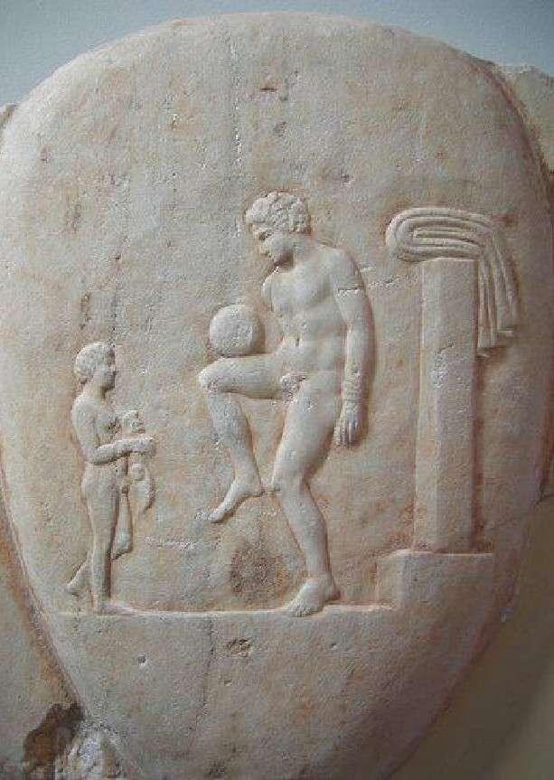 Μαρμάρινη εικόνα στην οποία απεικονίζεται ένας αρχαίος Έλληνας να ισορροπεί μία μπάλα με το πόδι του. Έκθεμα στο Εθνικό Αρχαιολογικό Μουσείο Αθηνών.