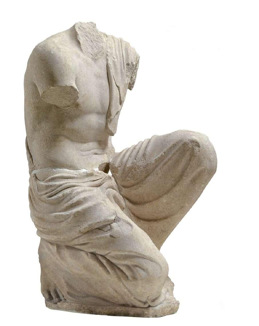 Ακέφαλη γονατιστή ανδρική μορφή από το ιερό του Οινομάου. Αρχαιολογικό Μουσείο Ολυμπίας. A headless kneeling male figure from the sanctuary of Onamoom. Archaeological Museum of Olympia.