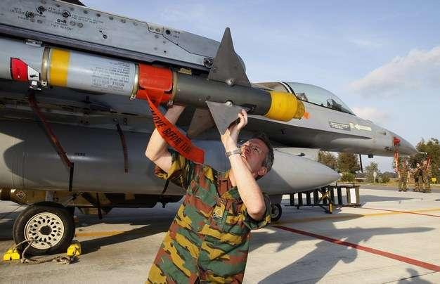 Βέλγος τεχνικός του στρατού εξετάζει ένα βλήμα AIM-9M αέρος-αέρος προσαρτημένο σε μαχητικό αεροσκάφος F16 της Βελγικής Πολεμικής Αεροπορίας, το οποίο συμμετείχε σε επίθεση στην Λιβύη, στην αεροπορική βάση του Αράξου, στις 28 Μαρτίου 2011. REUTERS/Yves Herman
