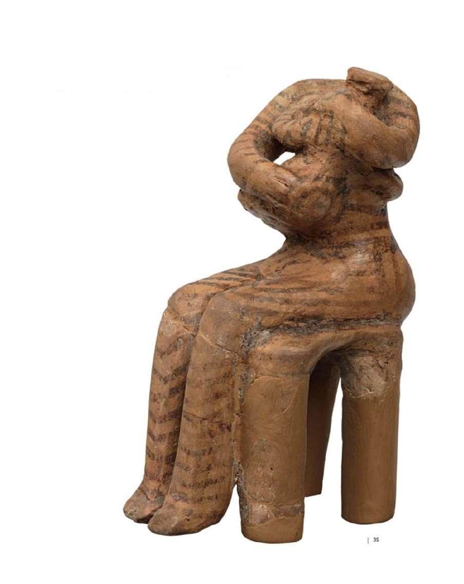 """Η «Κουροτρόφος». Πήλινο ειδώλιο γυναίκας με βρέφος στην αγκαλιά, καθιστής σε σκαμνί, στην ύστατη φάση της προετοιμασίας για τον θηλασμό. Μοναδικό δείγμα πλαστικής της νεότερης Νεολιθικής Περιόδου (4800-4500 π.Χ.) Νεολιθικός οικισμός στο Σέσκλο Μαγνησίας. The """"Courotroph"""". Clay figurine of a woman with a baby in her arms, sitting in a stool, in the final phase of preparation for breastfeeding. Unique sample of plastic of the newer Neolithic Period (4800-4500 BC) Neolithic settlement in Sesklo, Magnesia."""