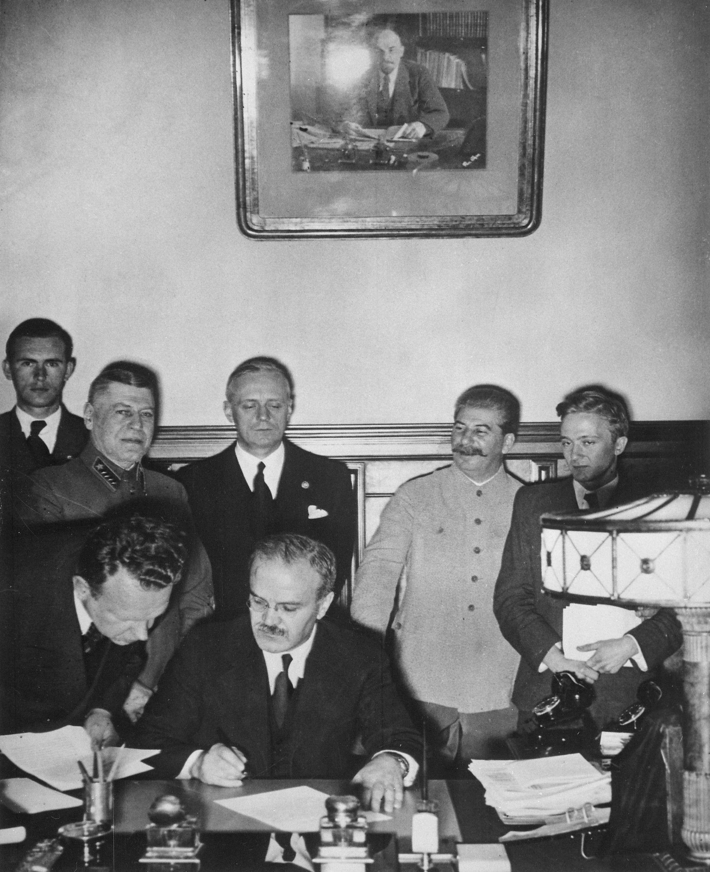 Ο Μόλοτοφ (υπογράφοντας), ο Ρίμπεντροπ (με τα μαύρα πίσω από τον Μόλοτοφ) και ο Στάλιν (δεξιά) στις 23 Αυγούστου 1939.