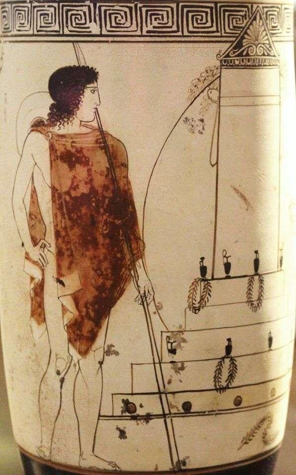 Νεαρός πολεμιστής επισκέπτεται τον (δικό του?) τάφο, κατάφορτο με ληκύθους και στεφάνια προς τιμήν του νεκρού. Λεπτομέρεια αττικής λευκής ληκύθου του Ζωγράφου του Bosanquet. Από την Ερέτρια, 450-440 π.Χ. Αθήνα, Εθνικό Αρχαιολογικό Μουσείο, Συλλογή Αγγείων. VISIT TO THE TOMB. Younq warrior is visiting (his?) tomb, which is covered with lekythoi (funerary vases) and wreaths in honour of the deceased. Detail from an Attic white-ground lekythos by the Bosanquet Painter. From Eretria, 450-440 BC. Athens, National Archaeological Museum, Vase Collection