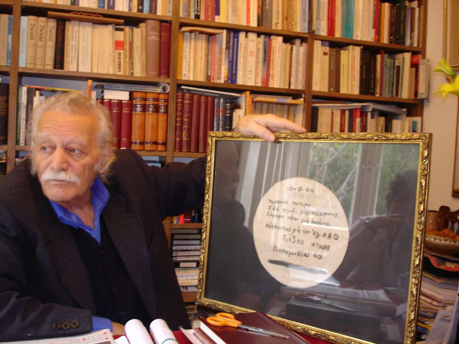 Ο Μανώλης Γλέζος με κορνιζαρισμένο το σημείωμα του εκτελεσμένου από τους Ναζί αδελφού του Νίκου, που έστειλε στην μητέρα τους (Αρχείο Δαμιανού Βασιλειάδη).