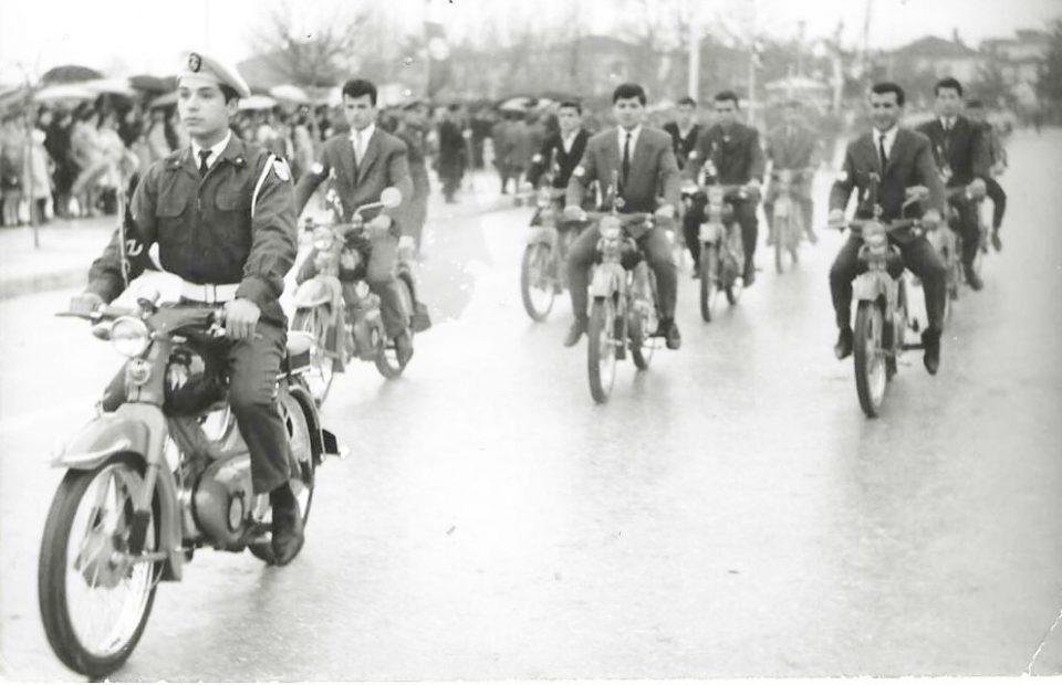 Βροχερή και κρύα μέρα ήταν η επέτειος της 25η Μαρτίου το1962. Με φόντο το γνωστό Τρία Άλφα οι συμπολίτες μας με τις θρυλικές φλωρέτες είναι έτοιμοι για την παρέλαση. Και ξεκινούν περνώντας μπροστά από το κτίριο της νομαρχίας, ενώ η Φιλαρμονική του δήμου παιανίζει εμβατήρια.